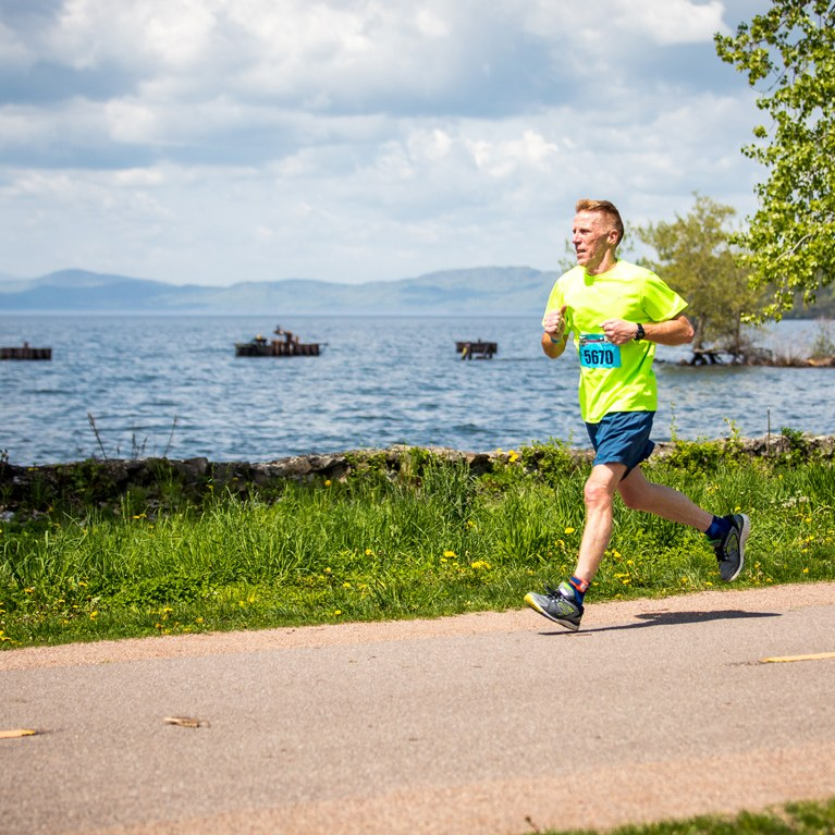 Runner running by lake champlain